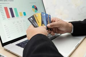 asiatische Buchhalter arbeiten berechnen und analysieren Bericht Projektbuchhaltung mit Notebook und Kreditkarte in modernen Büro foto