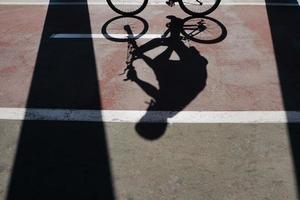 Radfahrer Schatten auf der Straße foto