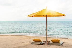 Dolden und Stuhl am tropischen Sommerstrandhintergrund foto
