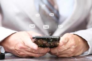 Hände mit dem Handy zum Abrufen von E-Mails foto