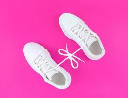 Paar weiße Sportschuhe verbunden mit Schnürsenkelbogen auf rosa Hintergrund foto
