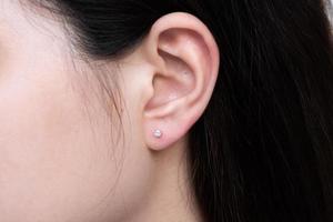 Diamantohrring am Ohr einer asiatischen Frau foto