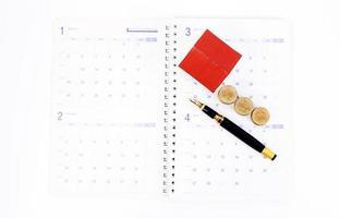 Füllfederhalter und Münzen und Papierhaus auf Kalenderbuchseiten für Hypothekendarlehensplanungskonzept foto