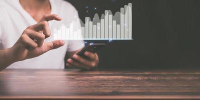 Konzept eines Geschäftsinvestors, der in der Online-Welt arbeitet und Hologrammgrafiken zeigt foto