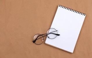 flaches Draufsichtfoto der Brille und des Notizblocks auf einem beigen Hintergrund foto