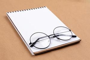 flaches Draufsichtfoto der Brille und des Notizblocks auf einem beigen abstrakten Hintergrund mit minimalem Stil des Kopierraums foto