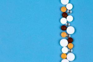 mehrfarbige Pillen auf einer Nahaufnahme des blauen Hintergrunds foto
