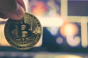 Finger halten Bitcoin-Münze mit einem unscharfen Hintergrund foto