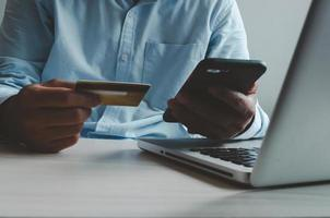 Mann, der ein Smartphone und eine Kreditkarte vor einem Laptop hält foto