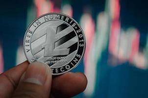 Mann, der Kryptowährung litecoin Münze mit einem virtuellen Börsendiagrammhintergrund hält foto