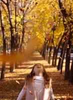 schönes kleines Mädchen, das gefallene Blätter wirft, die im Park mit herbstlichem Naturhintergrund spielen foto