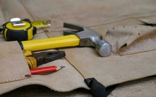 Sammlung von Holzbearbeitungswerkzeugen in Lederschürze auf einer rauen Holzwerkbank foto