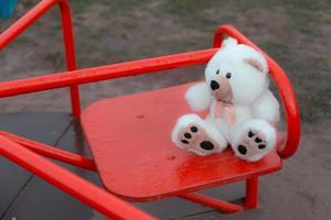 Nahaufnahme eines Teddybären, der auf einer Kinderschaukel sitzt foto