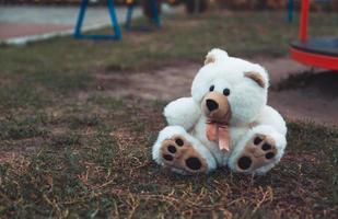verlassener weicher Plüsch ausgestopfter Teddybär sitzt auf dem Boden foto