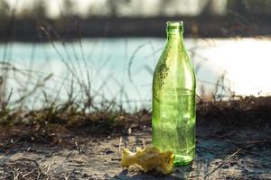 schmutzige Glasflasche im Wald neben einem Apfelstummel foto