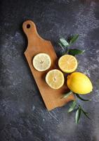 Zitronen und grüne Blätter auf hellem schwarzem Hintergrund foto
