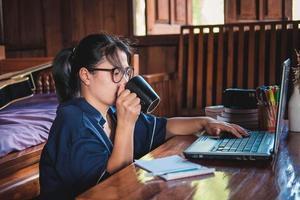 Frau, die einen Kaffee auf einem Boden im Haus sitzt, der Notizen aufschreibt, öffnete Laptop vor ihrem Home-Office-Konzept foto