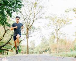 gesunder Mann, der auf Spur im Park läuft foto