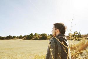 Ein junger Mann, der von hinten steht und in Ruhe die morgendliche Herbstsonne auf einem Pfad eines gelben Feldes mit der Hintergrundbeleuchtung des blauen Himmels genießt foto