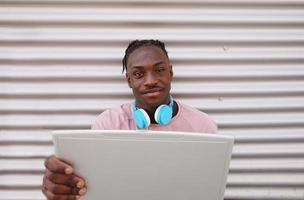 junger Mann, der mit seinem Laptop arbeitet foto