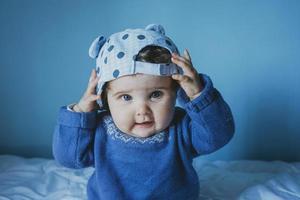 kleines Baby spielt mit einer Mütze foto