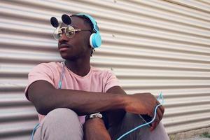 junger Mann, der Musik mit seinem Smartphone hört foto