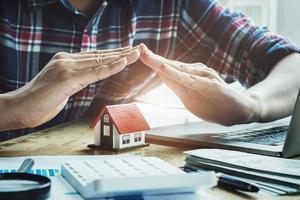Versicherungsvertreter hebt seine Hand, um ein Haus unter seinen Händen zu schützen foto