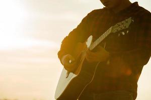 asiatische Mannakustikgitarre mit Schattenbild mit Sonnenunterganghintergrund foto