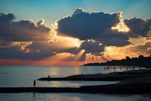 Wellenbrecher und Menschen Silhouette auf dem Hintergrund eines hellen Sonnenuntergangs foto