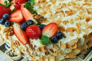 Erdbeer-Baiser-Kuchen mit Mandelblättern auf Zeitung foto