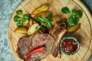 Knochenlende mit Kartoffeln und Basilikum roter Sauce foto