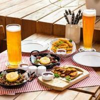 leckeres Fleischmahlzeit-Roulette mit Zitronen-Sprotte und Bier auf dem Restauranttisch foto