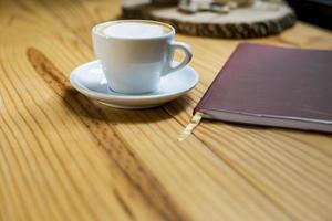 Notizbuch mit Tasse Kaffee auf Holzschreibtisch foto