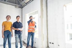 junges asiatisches Paar, das Haus mit Vorarbeiteringenieur während der Hausinspektion überprüft foto
