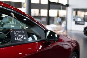 rotes Auto im Autohausverkauf, wegen Sperrung der Coronavirus-Krankheit geschlossen foto