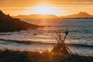 ein Lagerfeuer am Strand während eines farbenfrohen Sonnenuntergangs darüber foto