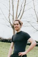 ein junger athletischer Mann, der zur Kamera lächelt, während Übung im Park mit Kopierraum und Kopfhörern tut foto