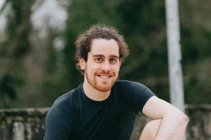 ein junger athletischer Mann, der zur Kamera lächelt, während er Sport im Park macht foto