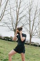 Ein junger athletischer Mann, der Kopfhörer benutzt, während er im Park mit der Maske trainiert foto