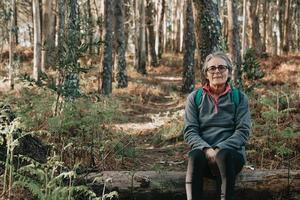 alte Frau, die über einem Koffer sitzt, der zur Kamera im Wald während eines herbstlichen Tages mit Kopierraum-Wellness-Trekking eines Joggingkonzepts lächelt foto