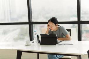 schöner lächelnder Frauenvideoanruf auf Handy während während der Arbeit am Laptop foto