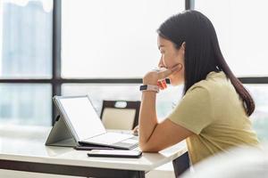 nachdenkliche Frau, die zu Hause am Tablet-Computer arbeitet foto