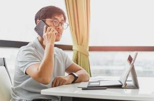 Mann, der auf Mobiltelefon spricht, während Laptop-Computer arbeitet foto