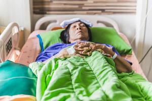 ältere Patientenhand mit Injektionssalzlösung, die im Krankenhausbett liegt foto