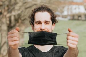 ein junger Mann, der eine schwarze Gesichtsmaske hält, während er im Park während des problemselektiven Fokus trainiert foto