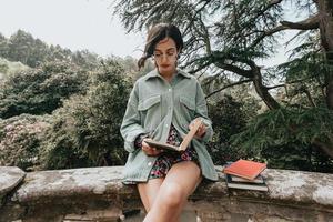 junge Frau, die auf einem alten Gebäude sitzt, das ein Buch während eines sonnigen Tages mit Kopienraumlebensstil- und Glückskonzept liest foto