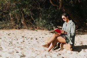 junge marokkanische Frau auf modernen Kleidern unter Verwendung der Sonnenbrille, die am Strand sitzt und ein Buch während eines sonnigen Tages mit kopierendem Rauminspirations- und Entspannungsthema mit bunten Tönen liest foto