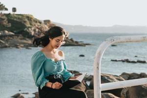 junge Frau, die zur Kamera lächelt, während sie am Strand während eines Supersonnenuntergangs liest, während sie eine Maske verwendet, die sich entspannt und inspirierende Konzepte mit buntem Kopierraumlebensstil verwendet foto