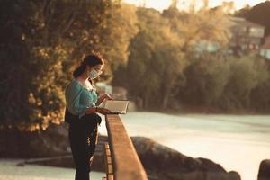 junge Frau, die am Strand während eines Super-Sonnenuntergangs liest, während eine Maske sich entspannt und inspirierende Konzepte mit buntem Lebensraum des Kopierraums verwendet foto