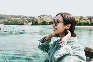 junge Frau in einem Bootssteg, der während eines sonnigen Tages lächelt, während Sonnenbrillenstrandtag verwendet wird foto